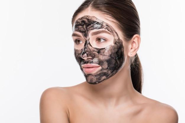 粘土または白い壁に分離された彼女の顔に泥マスクを持つ美しい女性 無料写真