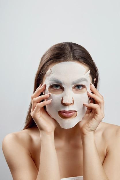 얼굴에 천 보습 마스크와 아름 다운 여자. 페이셜 및 스파 트리트먼트. 화장품 마스크. 프리미엄 사진