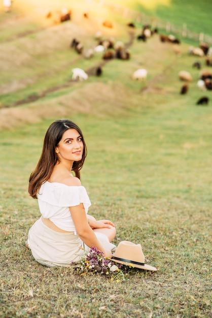 牧草地の帽子を持つ美しい女性 Premium写真