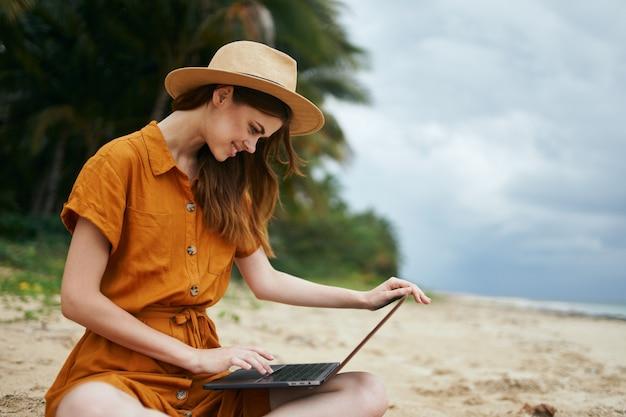 砂の上に座っているラップトップを持つ美しい女性と作品 Premium写真