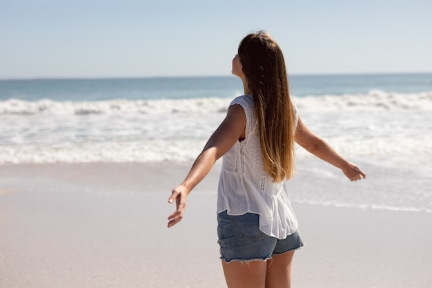 Beautiful woman with arms stretched out standing on beach in the sunshine Free Photo