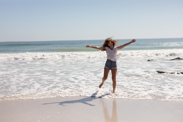 Beautiful woman with arms stretched out walking on beach in the sunshine Free Photo