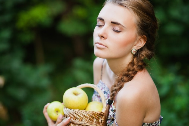 Beautiful woman with basket full of apples Premium Photo