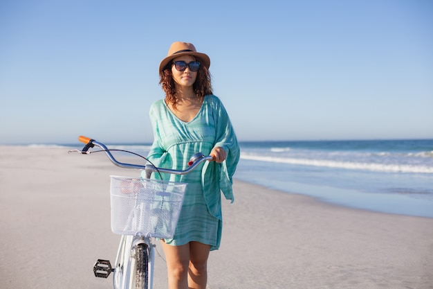 Beautiful woman with bicycle walking on beach in the sunshine Free Photo