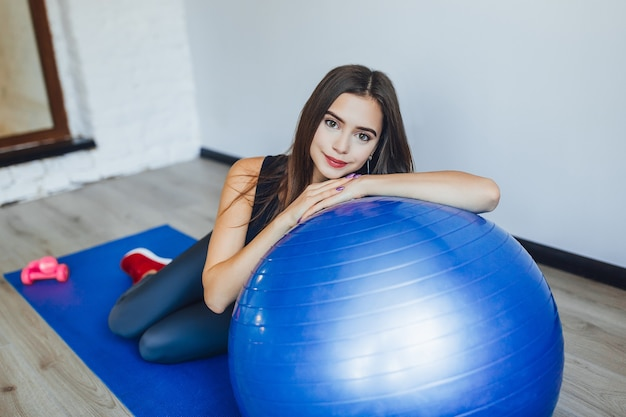 Красивая женщина с синим мячом для йоги лежит на нем и смотрит в камеру Premium Фотографии