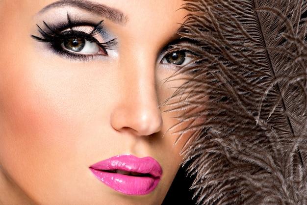 얼굴 근처에 깃털을 가진 밝은 전문 메이크업으로 아름 다운 여자. 무료 사진