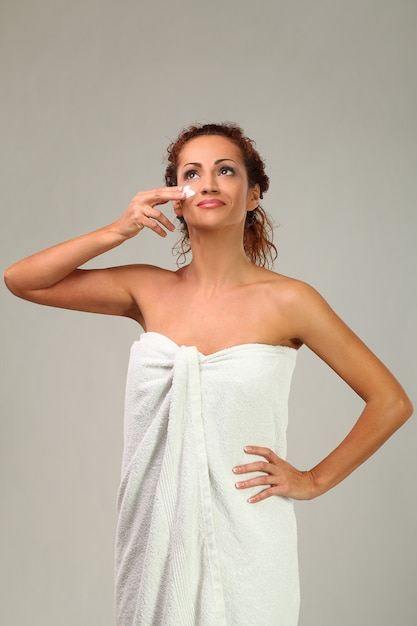 Beautiful woman with cream on face Free Photo