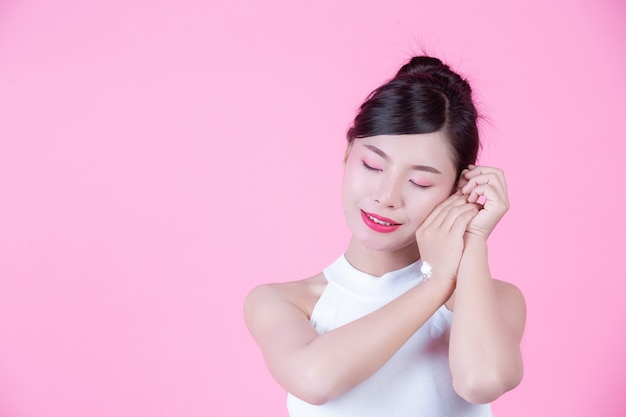 Beautiful woman with cream on the skin on a pink background. Free Photo
