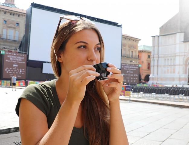 日当たりの良いイタリアの風景にコーヒーのカップを持つ美しい女性 Premium写真