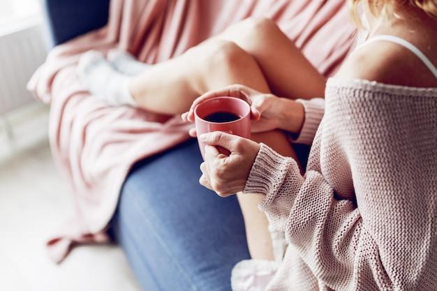 ソファの上のコーヒーのカップを持つ美しい女性 無料写真