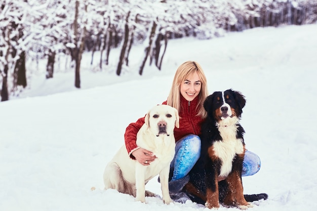 The beautiful woman with dog sitting on the snow Free Photo