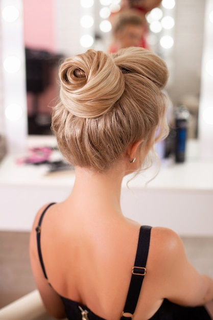 Beautiful woman with fashion hairstyle looking at the mirror in hairdressing salon Premium Photo