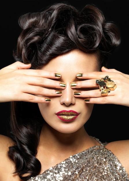 金色の爪と創造的な口紅を持つ美しい女性。黒い壁にスタイルの髪型を持つブルネットの女の子モデル 無料写真