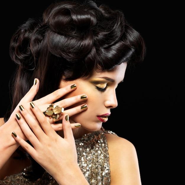 金色の爪と目のファッションメイクを持つ美しい女性。黒い壁にスタイルの髪型を持つブルネットの女の子モデル 無料写真