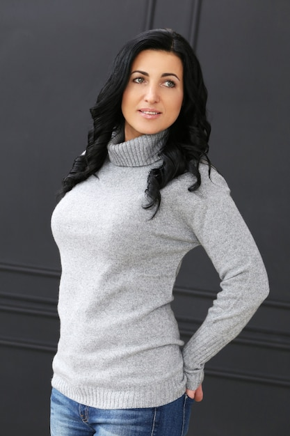 Beautiful woman with grey sweater and jeans Free Photo
