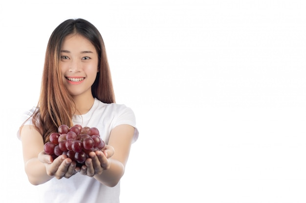 Beautiful woman with a happy smile holding a hand grape, isolated on white background. Free Photo