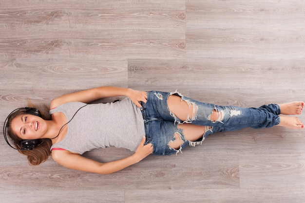Beautiful woman with headphones lying on the floor Free Photo