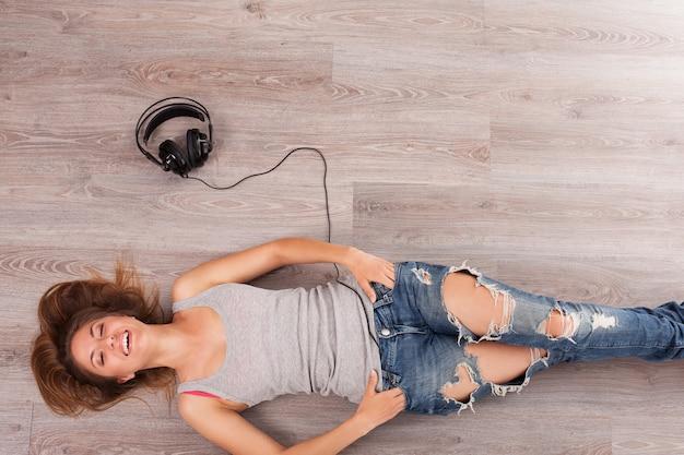 Beautiful woman with headphones lying on the floor Free Photo