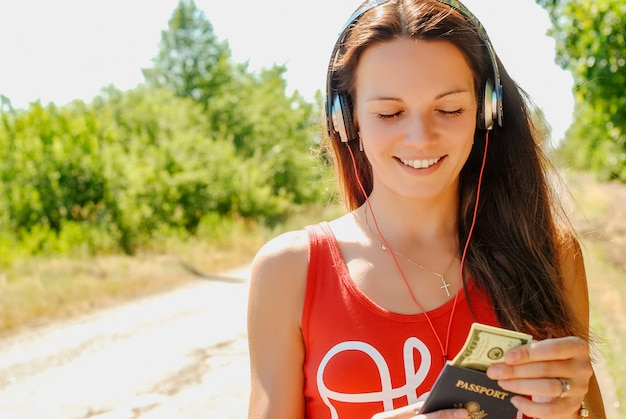 Beautiful woman with headphones on the road holding a passport with money. Premium Photo