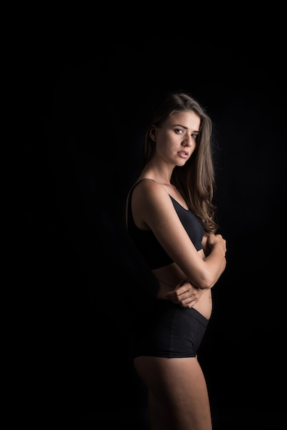 Beautiful woman with healthy body on black background Free Photo