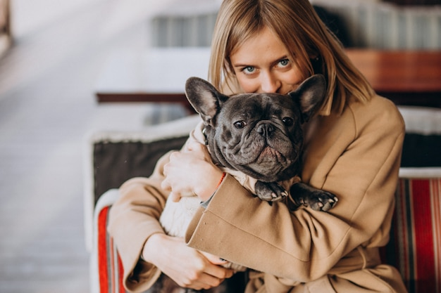 Beautiful woman with her cute french bulldog in warm outfit Free Photo