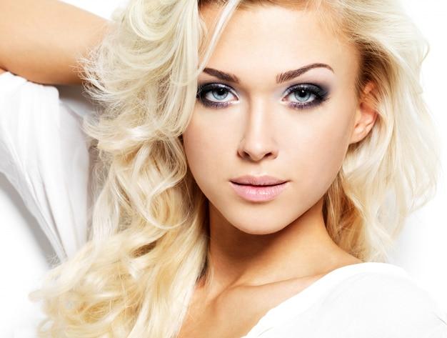 Bella donna con capelli ricci biondi lunghi. ritratto di modella con trucco luminoso. isolato su bianco Foto Gratuite