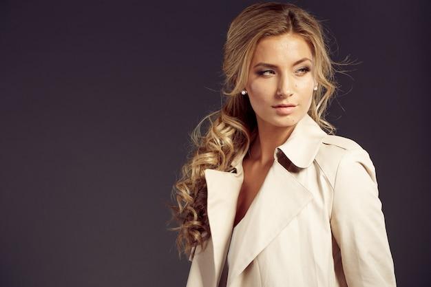Beautiful woman with long blond hair in beige fur coat Premium Photo