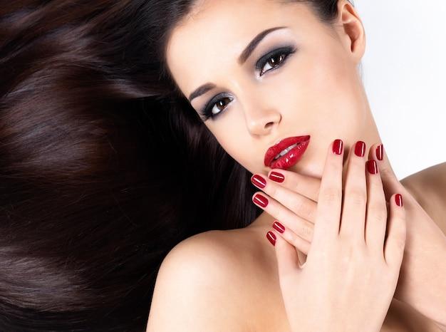 긴 갈색 직선 머리카락과 우아함 빨간 손톱을 가진 아름다운 여인 무료 사진