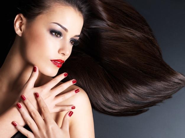 暗い壁に横たわっている長い茶色のストレートの髪と赤い爪を持つ美しい女性 無料写真