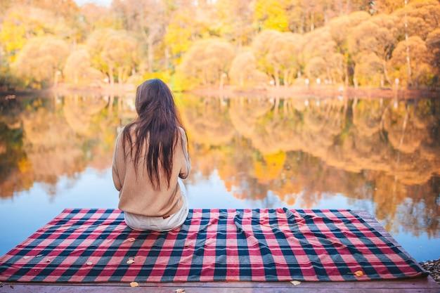 Красивая женщина с длинными волосами в осенний день на открытом воздухе отдыхает на пирсе Premium Фотографии