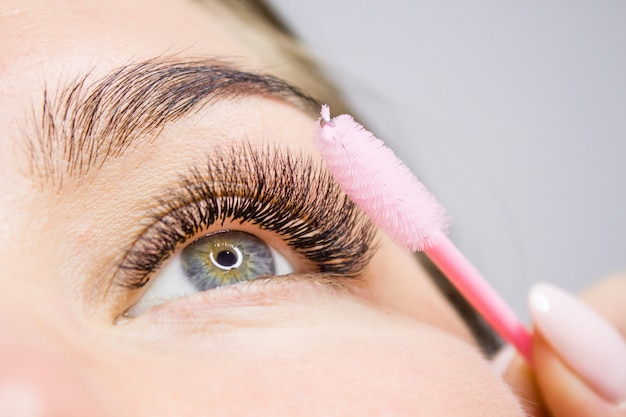 Beautiful woman with long lashes in a beauty salon. eyelash extension. Premium Photo