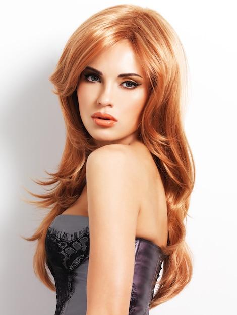 긴 직선 붉은 머리를 가진 아름 다운 여자입니다. 흰 벽에 패션 모델 무료 사진