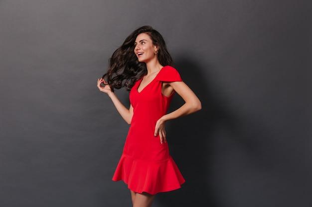 暗い背景に赤い服でポーズをとる壮大なウェーブのかかった髪の美しい女性。 無料写真