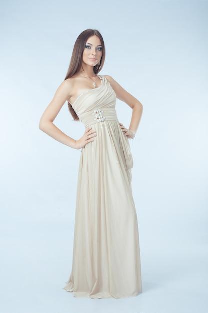 Красивая женщина с современным платьем позирует в студии Бесплатные Фотографии