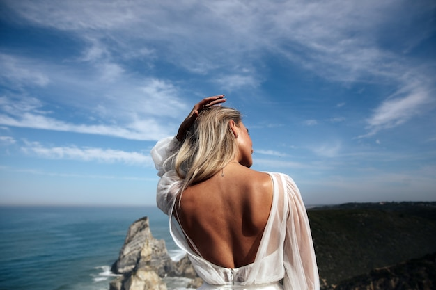 Beautiful woman with naked back stands on the panoramic coast view Free Photo
