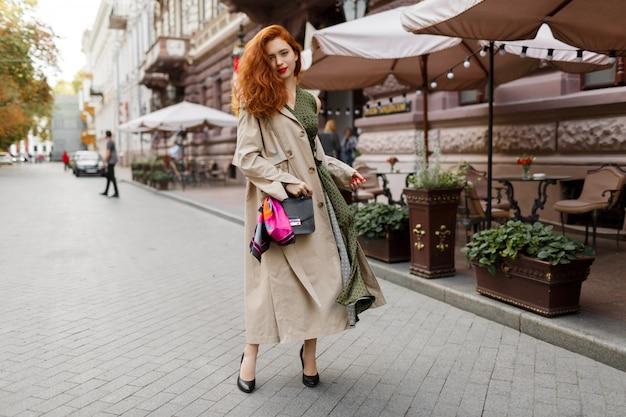 Красивая женщина с рыжими волосами и яркий макияж, ходить по улице. ношение бежевого пальто и зеленого платья. Бесплатные Фотографии