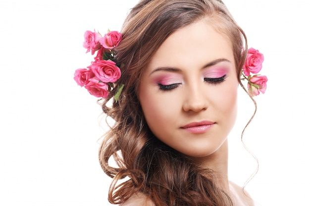 Beautiful woman with roses in hair Free Photo