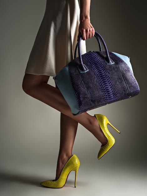 Bella donna con gambe sottili in tacchi alti gialli. la ragazza alla moda tiene la borsa blu alla moda. concetto elegante glamour. arte. la donna cammina dopo lo shopping. femmina irriconoscibile. Foto Gratuite