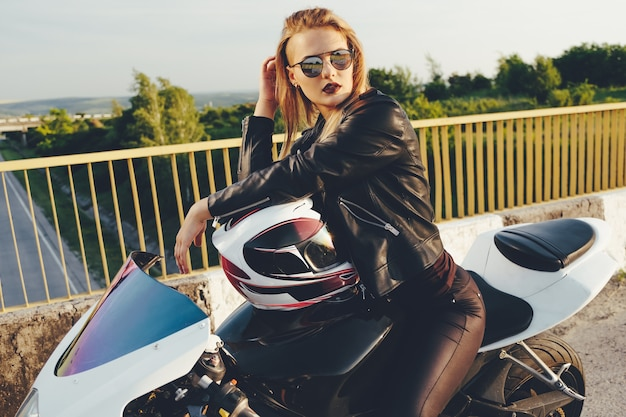 Beautiful woman with sunglasses driving on motorbike Free Photo