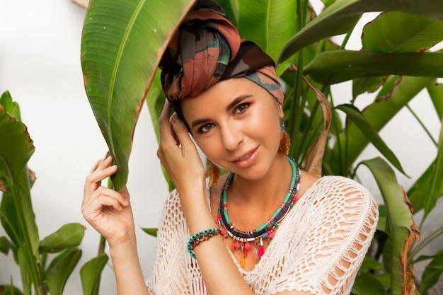 頭にターバン、カラフルなイヤリング、自由奔放に生きるネックレスポーズを持つ美しい女性 無料写真