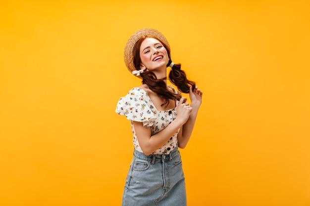 두 묶은 머리를 가진 아름 다운 여자는 반쯤 미소 짓는다. 모자, 여름 탑과 데님 스커트 오렌지 배경에 포즈에 여자. 무료 사진
