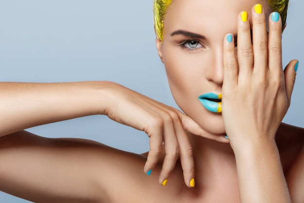 Beautiful woman with yellow hair and colorful nails and lips Premium Photo