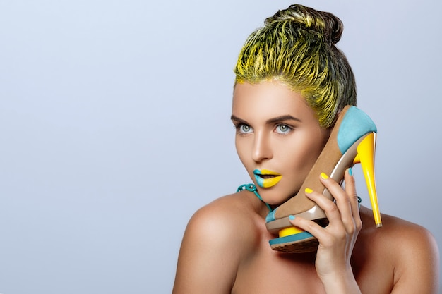 Beautiful woman with yellow holding colorful shoes Premium Photo