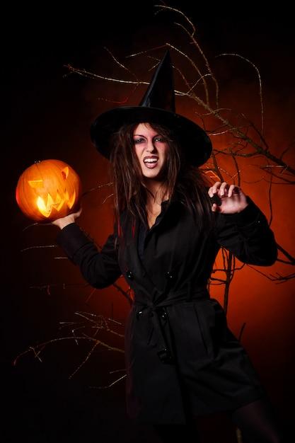 Una bella donna con una zucca in mano Foto Gratuite