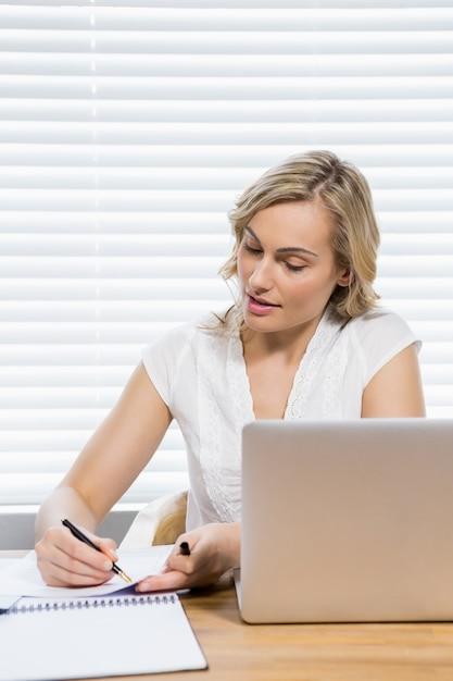 Beautiful woman writing on paper Free Photo