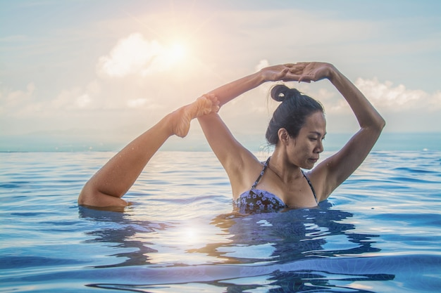 Красивая женщина-йога в бирюзовом голубом бассейне. Premium Фотографии