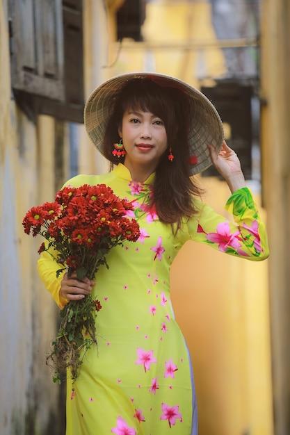 Beautiful women in ao dai vietnam traditional dress walking in the ancient city hoi an Premium Photo