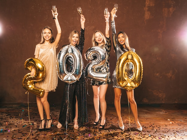 Beautiful women celebrating new year.happy gorgeous girls in stylish sexy party dresses holding gold and silver 2020 balloons, having fun at new year's eve party.сarrying and raising champagne flutes Free Photo
