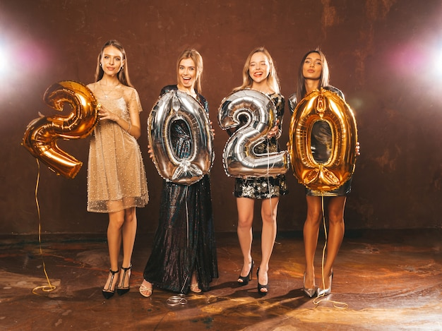 Beautiful women celebrating new year. happy gorgeous girls in stylish sexy party dresses holding gold and silver 2020 balloons, having fun at new year's eve party. holiday celebration.charming models Free Photo