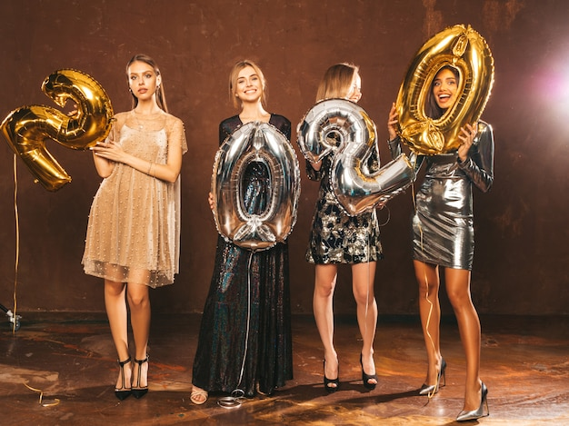 Beautiful women celebrating new year.happy gorgeous girls in stylish sexy party dresses holding gold and silver 2020 balloons, having fun at new year's eve party. Free Photo